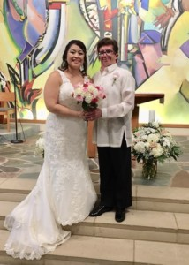 A wedding couple standing on the altar in a church. They took dance lessons for their Wedding First Dance at Prestige Ballroom Dancing.