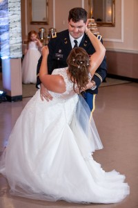 A groom in military uniform dipping his bride in her bridal gown. They took lessons at Prestige Ballroom Dancing.